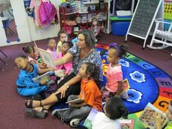 Woman reading a book to kids in an after school program