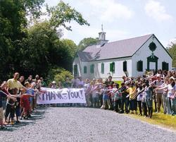 Summer campers holding a huge Thank You banner